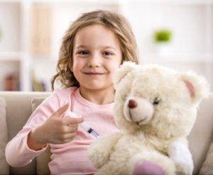 kleines Mädchen impft ihren Teddy mit Spielzeugspritze