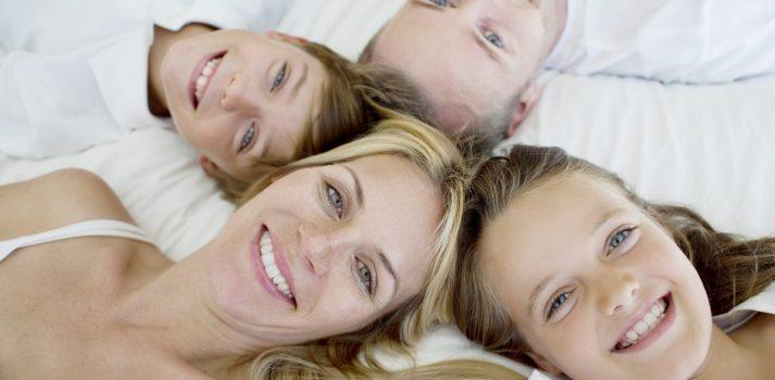 glückliche Familie liegt im Bett