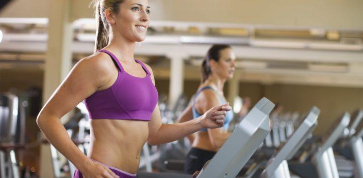 lächelnde Frau auf Laufband im Fitnessstudio