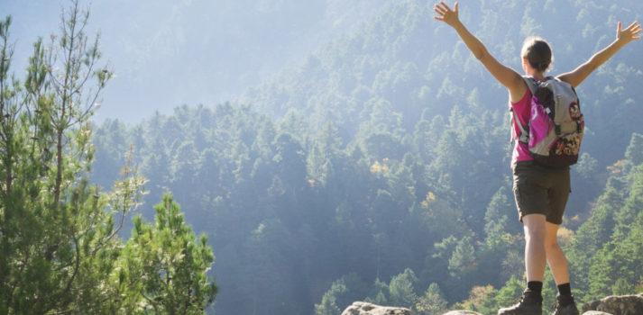 wandernde Frau steht auf Felsen und hält ihre Arme nach oben