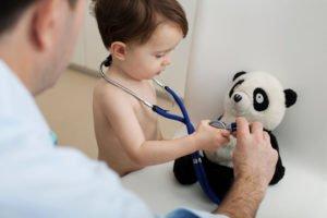 kleiner Junge hält Stethoskop an sein Panda-Kuscheltier