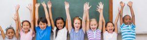 acht kleine Kinder stehen vor Tafel und halten ihre Arme in die Luft
