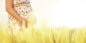 schwangere Frau steht im Getreidefeld