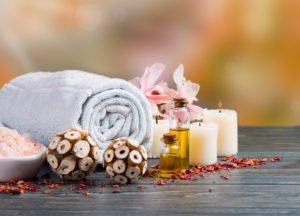 Wellnessfoto mit zusammengerolltem Handtuch, Ölen, Kerzen, Meersalz und Blumen