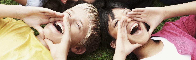kleiner Junge und Mädchen liegen auf der Wiese und rufen