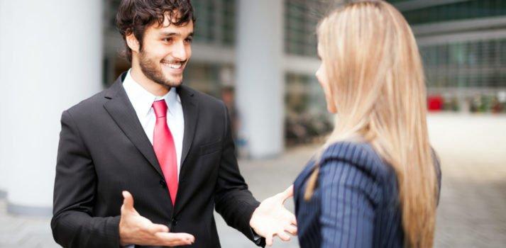 Mann im Anzug begrüßt Frau im Blazer