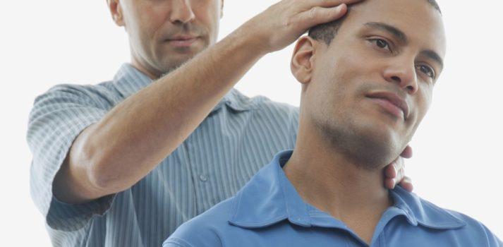 Mann hält Kopf und Nacken seines Patienten