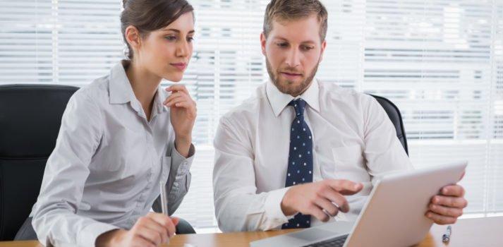 Mann in Businessoutfit erklärt Frau etwas am Laptop