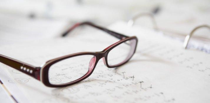 Nahaufnahme einer Brille auf Mathehausaufgaben