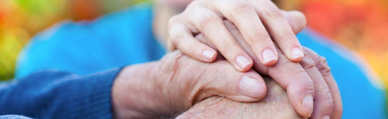 junge Frauenhand hält Hand von altem Mann