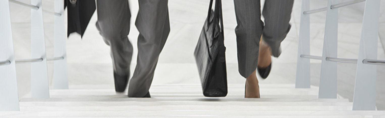 Frau und Mann im Business-Outfit laufen Treppe hoch