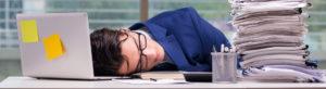 Mann im Anzug schläft am Arbeitsplatz neben einem großem Papierstapel