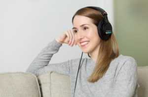 Frau sitzt lächelnd auf Sofa und hört Musik