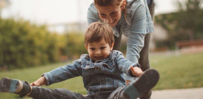 Frau schiebt Kind auf Skateboard