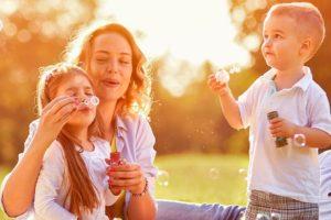 Familie sitzt auf Wiese mit Seifenblasen