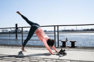 Frau macht Yogaübungen am Wasser