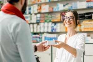 people buying medication at local pharmacy