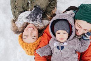 Familie liegt im Schnee, daneben liegt ein Schneemann