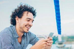 Mann sitzt auf Schiff und schaut ins Handy