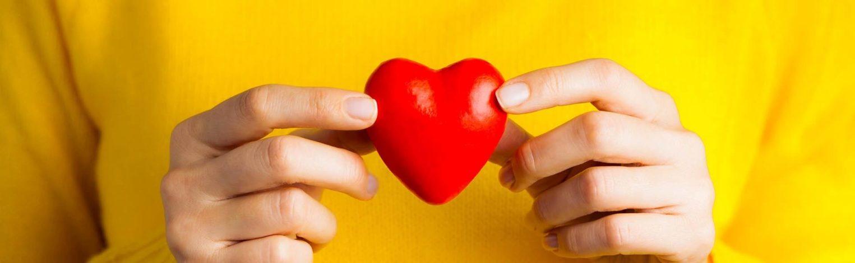 Frau mit gelben Pullover hält rotes Herz vor die Brust